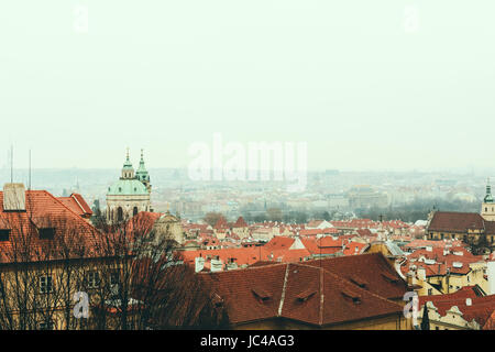 Bird's eye view of Prague skyline and St. Nicholas Church from the viewing platform near Prague Castle on a foggy - Stock Photo