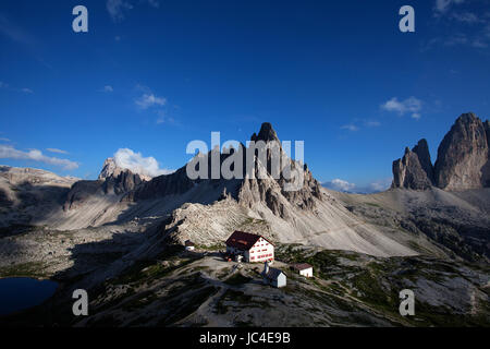 Colorful summer evening at the hut at Tre Cime di Lavaredo, Dolomites, Italy. - Stock Photo