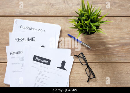 Resume applications on wooden desk ready to be reviewed - Stock Photo