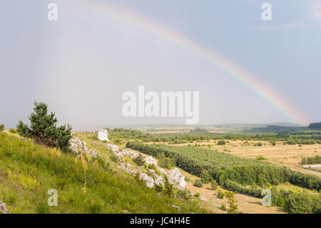 Rural landscape with rain and rainbow over fields - Stock Photo