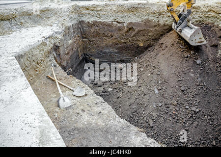 View on tools for ground work, spade and shovel crossed for the pause on building site. Excavator's tool, bucket - Stock Photo