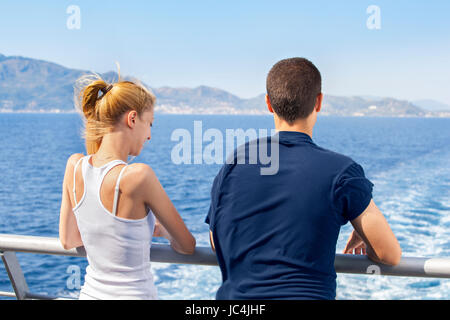 Two young people woman and man sailing on a ship and enjoying their summer sea vacation. - Stock Photo