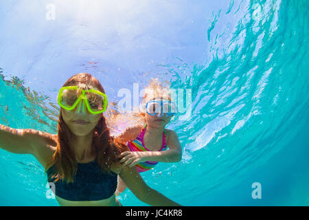 Happy family - mother with baby girl dive underwater with fun in sea pool. Healthy lifestyle, active parent, people - Stock Photo