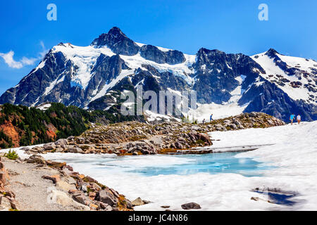 Hiking Mount Shuksan Blue Pool Hikers Artist Point Mount Baker Highway Washington Snow Mountain Grass Trees - Stock Photo