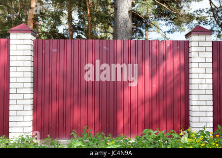 Fence made of metal panels red color outdoors - Stock Photo