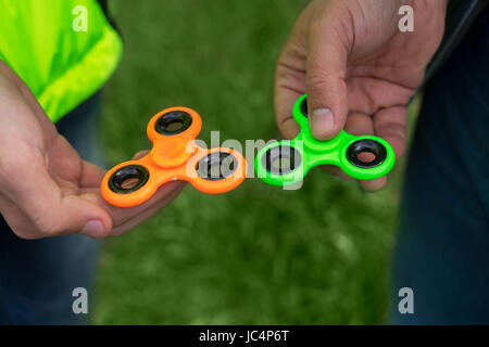 trendy fidget spinner - two persons holding green and orange fidget spinners in hands, close up view - Stock Photo