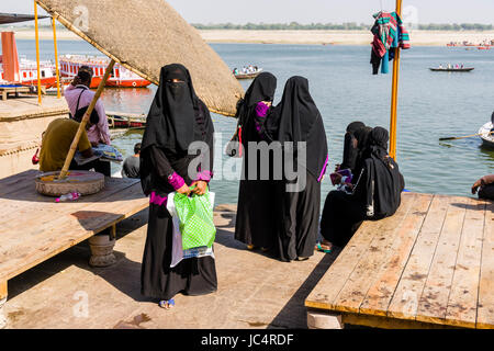 A group of muslim women, wearing black chadors, is visiting Dashashwamedh Ghat, Main Ghat, in the suburb Godowlia - Stock Photo