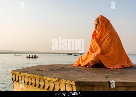A Sadhu, holy man, is sitting and meditating on a platform at the holy river Ganges at Dashashwamedh Ghat, Main - Stock Photo