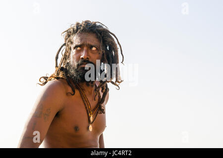 Portrait of a Sadhu, holy man, on a platform at the holy river Ganges at Meer Ghat in the suburb Godowlia - Stock Photo