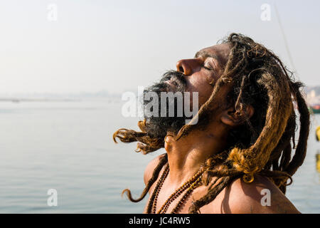 A Sadhu, holy man, is sitting and praying on a platform at the holy river Ganges at Meer Ghat in the suburb Godowlia - Stock Photo