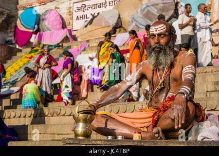 Portrait of a Sadhu, holy man, sitting on a platform at the holy river Ganges at Dashashwamedh Ghat, Main Ghat, - Stock Photo