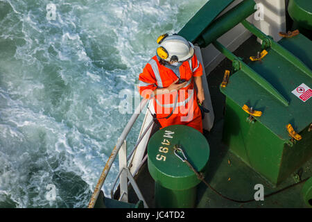 Female crew member with radio / walkie-talkie in orange overall and wearing safety helmet working on deck of car - Stock Photo