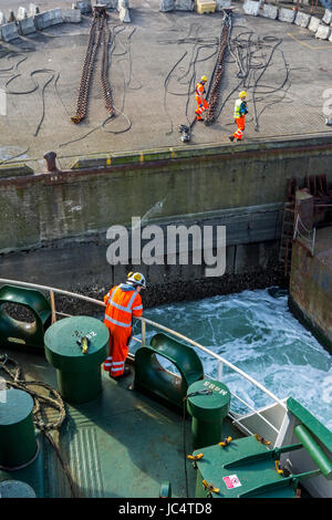 Female crew member in orange overall and wearing safety helmet working on deck of car carrier / cargo ship in seaport - Stock Photo