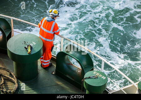 Female crew member in orange overall and wearing safety helmet working on deck of car carrier / cargo ship at sea - Stock Photo