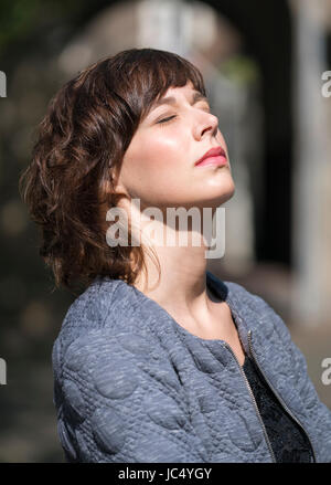 Beautiful young woman  with eyes closed enjoying the sunlight outdoors - Stock Photo