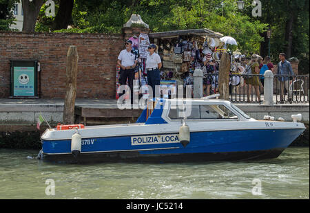 VENICE, ITALY - JUNE 13, 2017:  Two police officers operating a speed trap beside a busy stall selling tourist souvenirs - Stock Photo