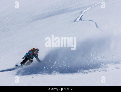Professional Snowboarder Robin Van Gyn, rides fresh powder on a sunny day while snowboarding in Haines, Alaska. - Stock Photo
