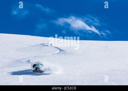 Professional Snowboarder and 2014 Olympic Gold Medalist, Jamie Anderson, rides fresh powder on a sunny day while - Stock Photo