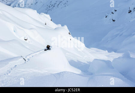 A snowboarder filmer sets up on a snow covered rock and crouches behind his camera to get a shot on a sunny day - Stock Photo