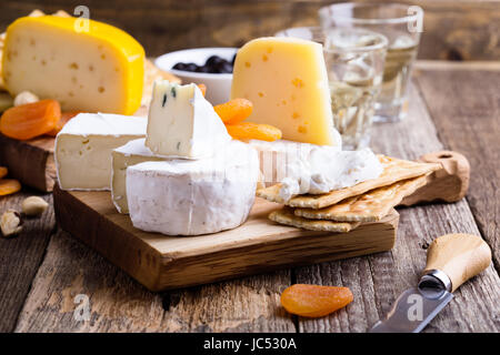 Cheese and wine party  table, perfect holiday appetizer on rustic wooden board - Stock Photo