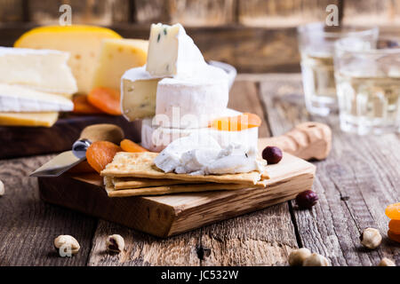Cheese and wine party  table, perfect holiday appetizer on rustic wooden board, goat cheese with  crackers - Stock Photo