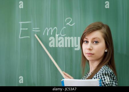 Student girl showing e=mc2 formula - Stock Photo