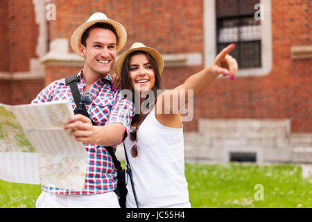 Woman pointing at something to her boyfriend during sightseeing - Stock Photo