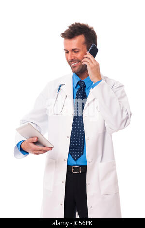 Doctor with mobile phone checking something on digital tablet - Stock Photo