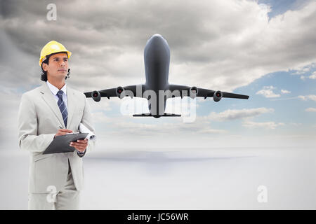 Composite image of attractive architect taking notes - Stock Photo