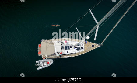 aerial view of a sailing boat on the Geneva lake, a zodiac attached to the boat and a lonely swimmer at the top - Stock Photo
