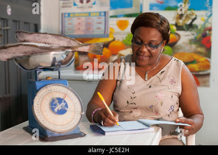 A small business owner, weighing out fish on her scales, Nigeria, Africa - Stock Photo