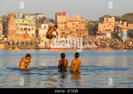 Young men are having fun and jump on the sand banks at the holy river Ganges, panorama of Dashashwamedh Ghat, Main - Stock Photo