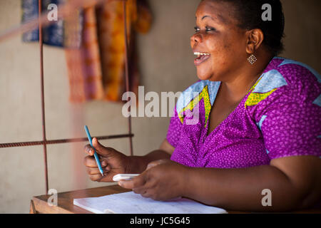 A female small business owner doing some book keeping, Tanzania, Africa - Stock Photo