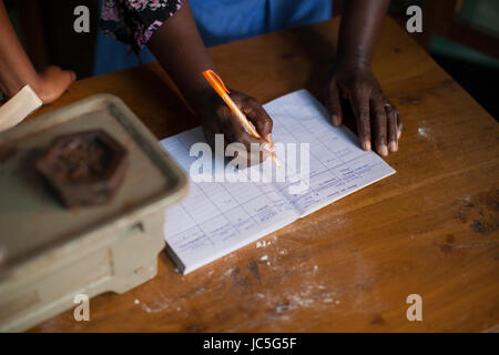 A female small business owner doing some book keeping, Tanzania, Africa. - Stock Photo