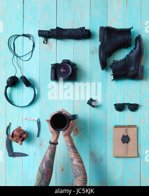 Set of cool things for travel on a blue wooden background With female hands with tattoos holding a cup of coffee - Stock Photo