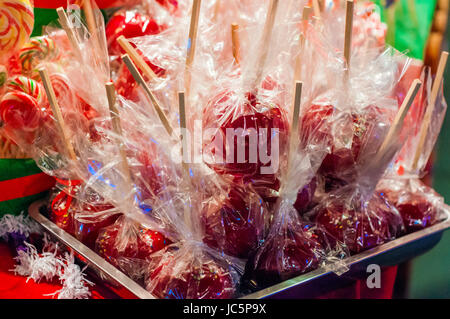 Sweet glazed red toffee candy apples on sticks for sale on farmer market or country fair. Delicious red candy apples covered with colorful sprinkles.  Stock Photo