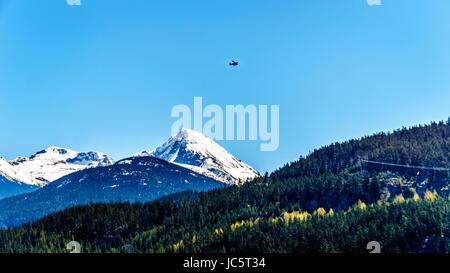 Small plane flying over Green Lake near Whistler British Columbia, Canada, with the snow caped peak of Wedge Mountain - Stock Photo