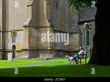 Man and dog and St Edward's's Church, Stow on the Wold, Gloucestershire, England UK - Stock Photo