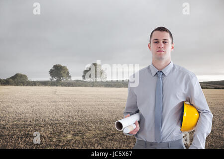 Composite image of architect carrying construction plan and helm in his office - Stock Photo
