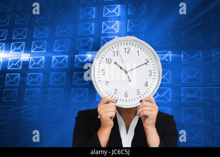 Composite image of businesswoman in suit holding a clock - Stock Photo
