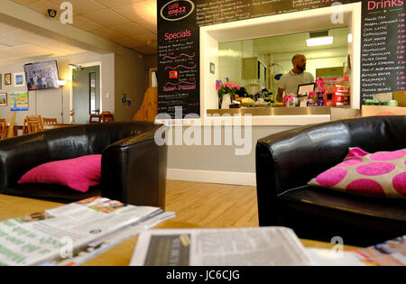 UK Cafe interior with comfy chairs and newspapers - Stock Photo
