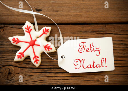 Feliz Natal, which is Portuguese and means Merry Christmas, on a Label with a red white Christmas Star Cookie - Stock Photo