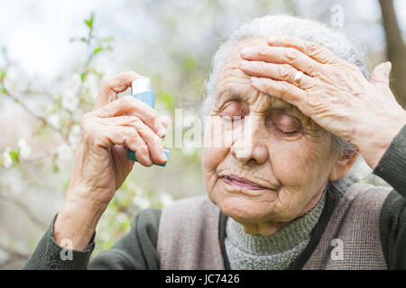 Close up picture of an elderly woman having an asthma attack, holding a bronchodilator - Stock Photo