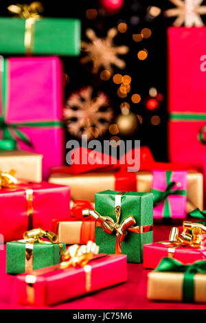 Many plain Christmas gifts arranged on a red cloth. Narrow depth of field. Mostly soft shapes in vibrant colors. - Stock Photo