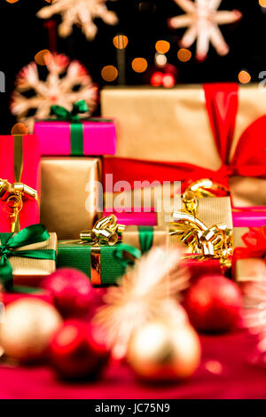 Plain Christmas gifts placed on a red cloth. All with bows and ribbons. Shallow depth of field. Tightly framed. - Stock Photo