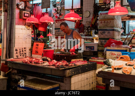 Colourful photo of a fishmonger filleting a fish on a round cutting board in his cramped stall in a wet market in - Stock Photo