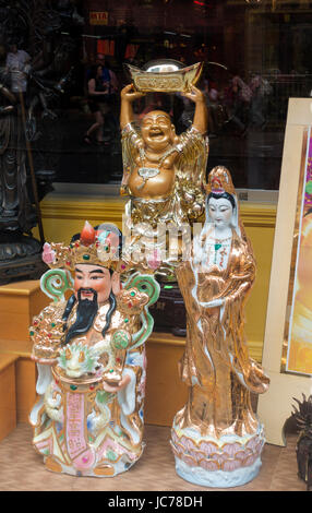 Small ornate figures in gold and other bright colors on display in the window of a shop in Chinatown, New York City - Stock Photo