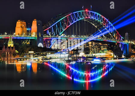 Multi colour arch of Sydney Harbour bridge with blurred reflection during Vivid Sydney festival in 2017. Blue light - Stock Photo