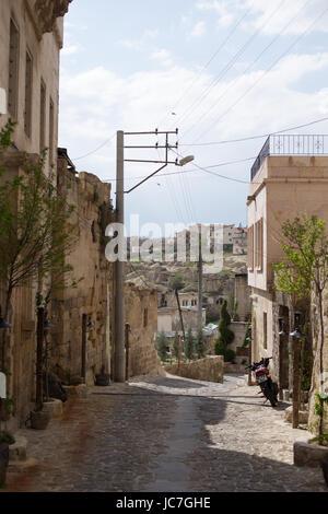 Narrow streets and stone houses with pebble road in Ortahisar of Cappadocia - Stock Photo