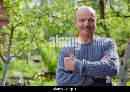 Mature man sitting in garden near apple tree in countryside. He shows thump up. - Stock Photo